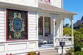 Historical white American house porch with stain glass window.