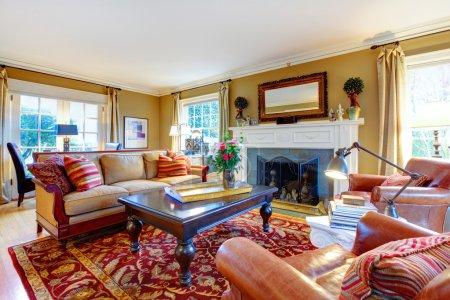 Photo pour Chambre familiale confortable avec des murs de ton clair, meubles à l'ancienne, table en marbre, tapis rouge classique et cheminée en arrière-plan dépoli - image libre de droit