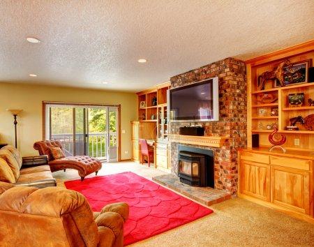 Photo pour Salon confortable avec combinaison de rangement et mur de briques avec cheminée et télévision. Chambre meublée avec chaise en cuir sans bras antique, canapé et salle d'amour , - image libre de droit