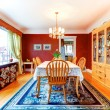 Red dining room with hardwood floor and rug. Furni...