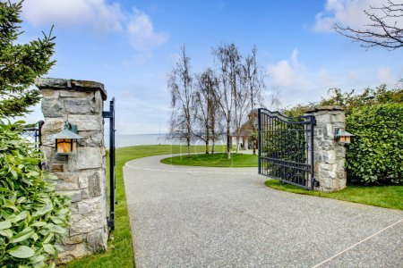Photo for Entrance iron gates with stone columns. View of driveway and roundabout. - Royalty Free Image