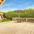 Spacious wooden deck with umbrella and patio table...