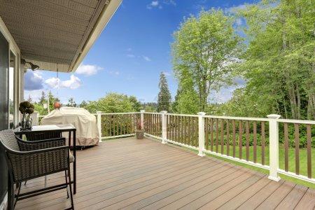 Photo pour Pont en bois avec balustrades blanches et brunes. Table de patio avec chaises en osier et barbecue - image libre de droit