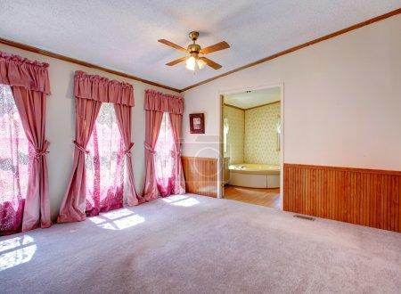 Photo pour Vide Chambre des maîtres avec porte ouverte à la salle de bain. Avis de traitement de fenêtre avec des rideaux rose - image libre de droit