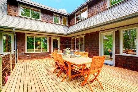 Photo pour Clapbord bardage maison marron avec terrasse en bois. Vue de la table rustique avec chaises - image libre de droit