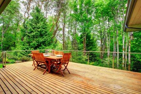 Photo pour Vue de la terrasse arrière avec table en bois servie et forêt verte - image libre de droit