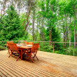 View of backyard deck with served wooden table  and green forest
