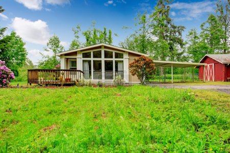 Photo for One story house with wooden deck, glass wall and attached pergola. House on farm land - Royalty Free Image