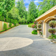 Beautiful driveway with three car garage. View of ...