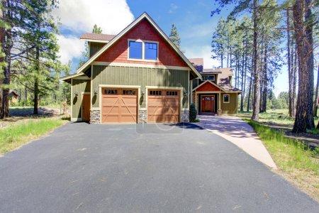 Foto de Casa de gran lujo con revestimiento verde y el naranja guarnición. vista del porche de entrada y garaje para dos coches - Imagen libre de derechos