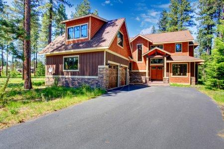 Foto de Casa de gran lujo con revestimiento marrón y naranja guarnición. vista del porche de entrada y garaje para dos coches - Imagen libre de derechos
