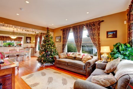 Photo for Cozy house interior on Christmas eve. View of living room with Christmas tree and dining area - Royalty Free Image