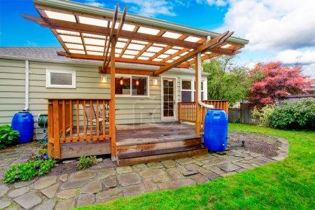 Photo pour Petite maison avec tablier de débrayage d'arrière-cour. vue de la terrasse en bois avec garde-corps et rock tuile passerelle - image libre de droit