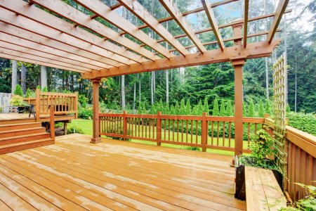Photo pour Spacieuse terrasse en bois avec bancs donnant sur la nature paysage - image libre de droit