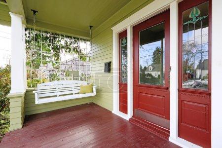 Photo pour Porche d'entrée dans la vieille maison aux murs verts et rouges de contraste. vue du swing de tenture en bois blanc - image libre de droit