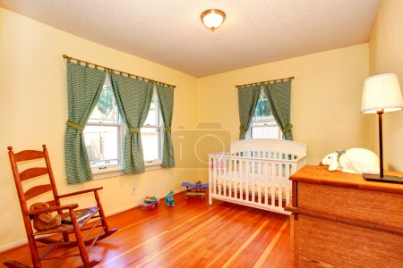 Cozy nursery room with crib and rocking chair