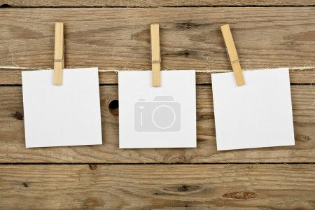 Photo for Three post-it notes hung with wooden clothes pegs - Royalty Free Image