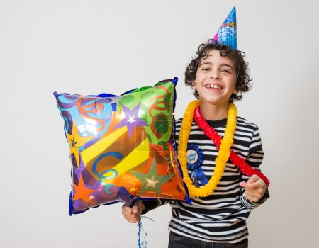 Child holding a balloon and smiling during his birthday party. Over grey background.