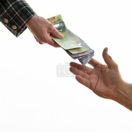 Photo pour Une femme donne de l'argent canadien à un homme. Sur fond blanc. Faire affaire entre les femmes et les hommes . - image libre de droit