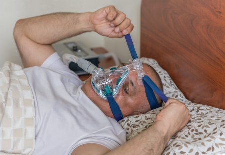 Photo for Man wearing a mask for treating sleep apnea. Mildly obese man suffering from sleep apnea and having a CPAP treatment - Royalty Free Image