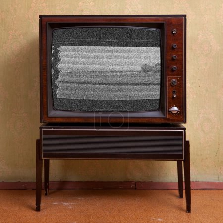 Photo for Retro TV on a background of vintage wallpaper in old room with vignetting - Royalty Free Image