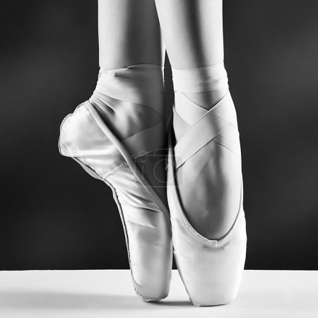 A photo of ballerina's pointes on black background