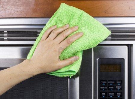 Photo pour Main avec chiffon microfibre nettoyage évents du four à micro-ondes - image libre de droit