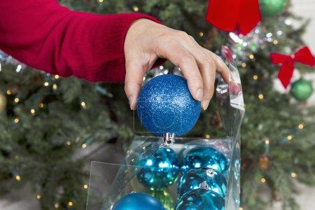 Photo pour Main femme ranger des ornements de fêtes pour terminer la saison avec arbre de Noël en arrière-plan - image libre de droit