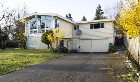 Photo pour Photo horizontale de l'ancienne maison résidentielle au début du printemps avec grande allée, cour avant et arbres nus - image libre de droit