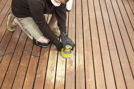 Mature man performing maintenance on home wooden deck