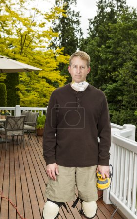 Photo pour Photo verticale de l'homme d'âge mûr se préparent à poncer une terrasse en bois extérieure avec meubles de patio et des arbres en arrière-plan - image libre de droit