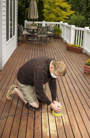 Photo pour Photo verticale de l'homme mature s'agenouiller pendant le ponçage pont de cèdre en bois extérieure avec meubles de patio et des arbres en arrière-plan - image libre de droit