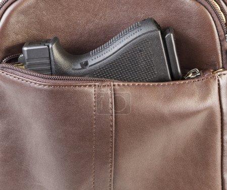 Photo pour Photo d'une arme personnelle moderne dans le sac à main de femme marron en cuir - image libre de droit