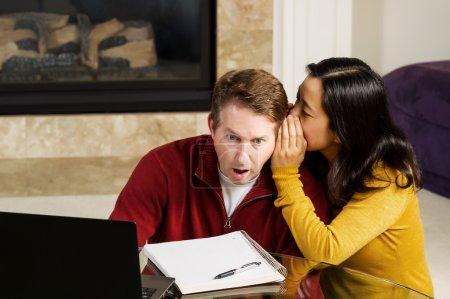 Photo pour Photo de couple mature avec femme chuchoter à l'oreille de l'homme qui est choqué, tout en travaillant de la maison avec cheminée et canapé partielle en arrière-plan - image libre de droit