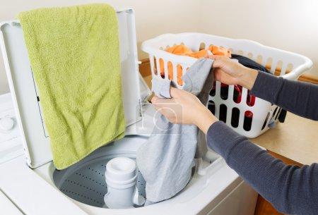 Photo pour Femelle photo horizontale mains mettre linge sale dans la machine à laver - image libre de droit