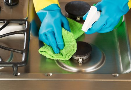 Gloved Hands Cleaning Stove Top Range with Spray bottle and Micr