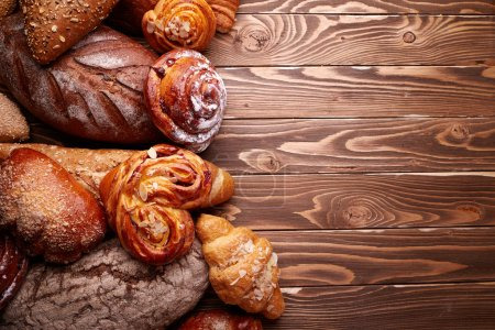Bread and buns over wooden background...