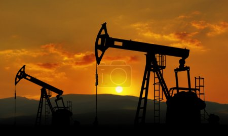 Photo for Oil field and pump jack against sunset - Royalty Free Image
