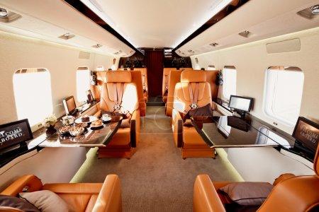 Photo pour Intérieur d'avion privé avec téléviseurs, sièges en cuir et tables en bois pour le déjeuner - image libre de droit