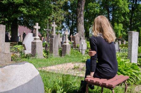 Sorrow woman near father husband tomb in cemetery
