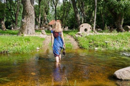 Photo pour Femme va étape par étape avec soin torrentielle flux d'eau se balance facilement en essayant de maintenir un équilibre - image libre de droit