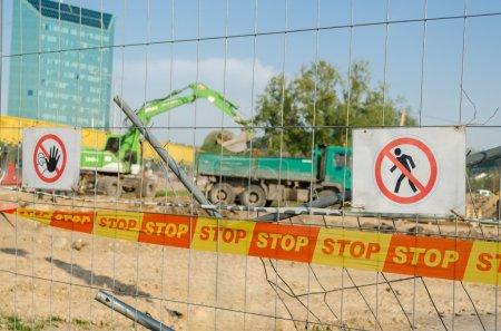 Photo pour Clôture de fer avec arrêt de bande de sécurité et avertissement ne pas entrer signe le chantier de construction dans la ville - image libre de droit