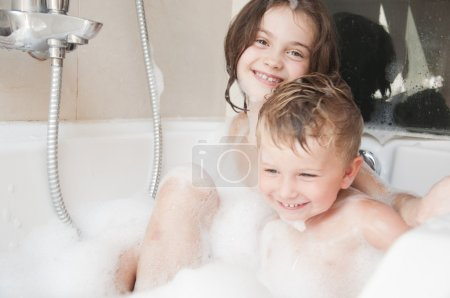 Brother and sister taking a bubble bath .