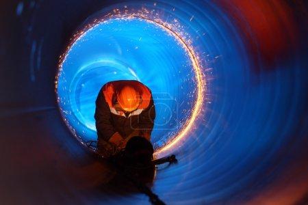 Photo pour Un travailleur travaille à l'intérieur d'un tuyau sur une construction de pipeline - image libre de droit