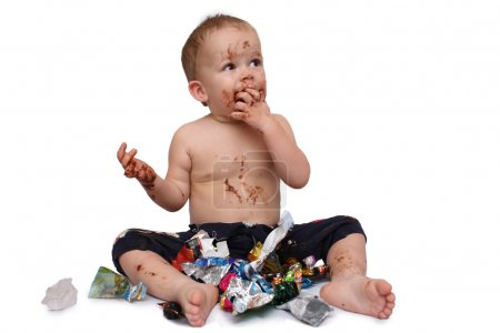Photo for Kid eats a lot of chocolate candies - Royalty Free Image