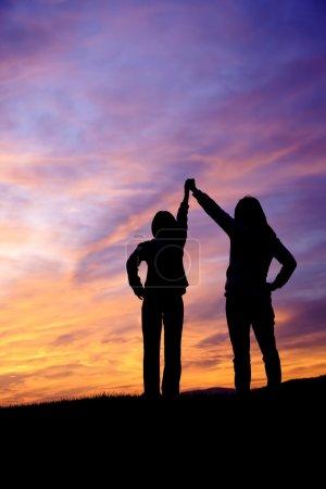Raising hands at sunset.