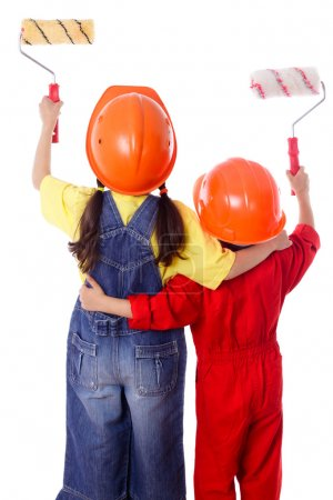 Two kids in coveralls with paint rollers
