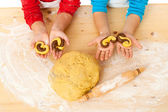 Child's hands with dough above the table