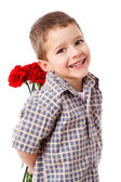 Smiling boy hiding a bouquet