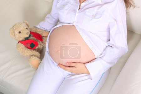 Mid section closeup of a pregnant woman holding her tummy